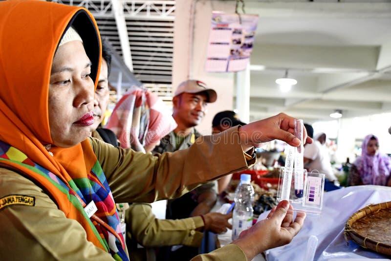 Ambtenaar van het handelsbureau terwijl het controleren van de chemische inhoud in voedsel stock fotografie