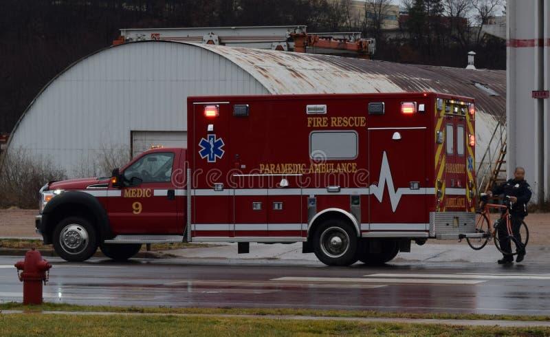 Ambulância de EMT Carrying Bike To na cena do acidente fotografia de stock