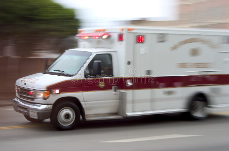 Ambulance #1. An ambulance blazes by, it's sirens whaling. An intentional camera blur gives a feeling of a rushed tension to the scene royalty free stock image