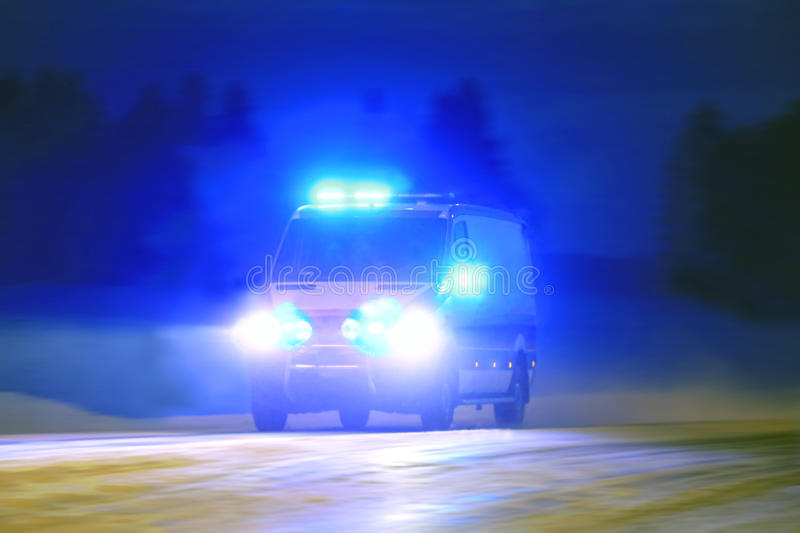 Ambulance in the Blue Night. Ambulance on emergency call with lights flashing in the blue night royalty free stock images