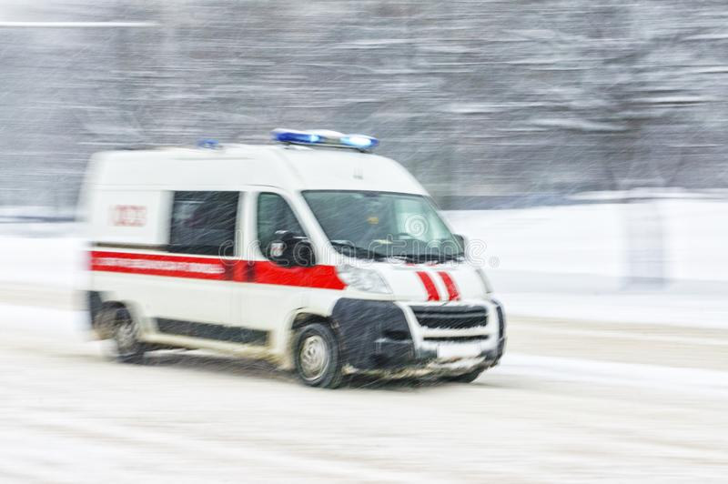 Ambulance car in snow storm. Driving in snow. Motion in blur ambulance car in heavy snowfall in city road. Abstract blur winter weather background royalty free stock photo
