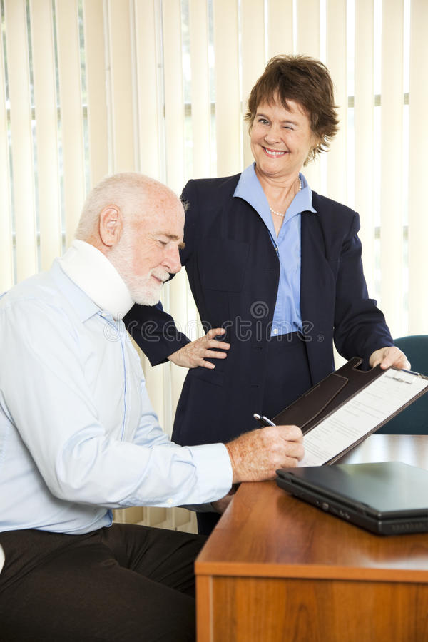 Ambulance Chasing Lawyer. Personal injury lawyer winks as she signs a gullible client stock photos