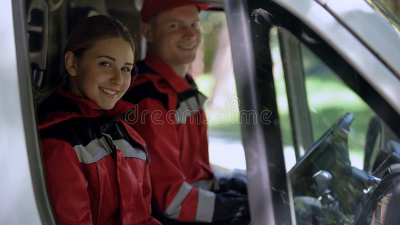 Ambulance crew looking into camera, sitting in transport, emergency services stock photography