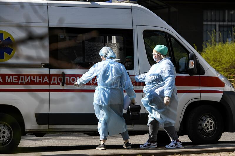 Ambulance doctors in protective suits against the coronavirus COVID-19 near ambulance car in Kyiv, Ukraine. April 2020. Ambulance doctors in protective suits royalty free stock image