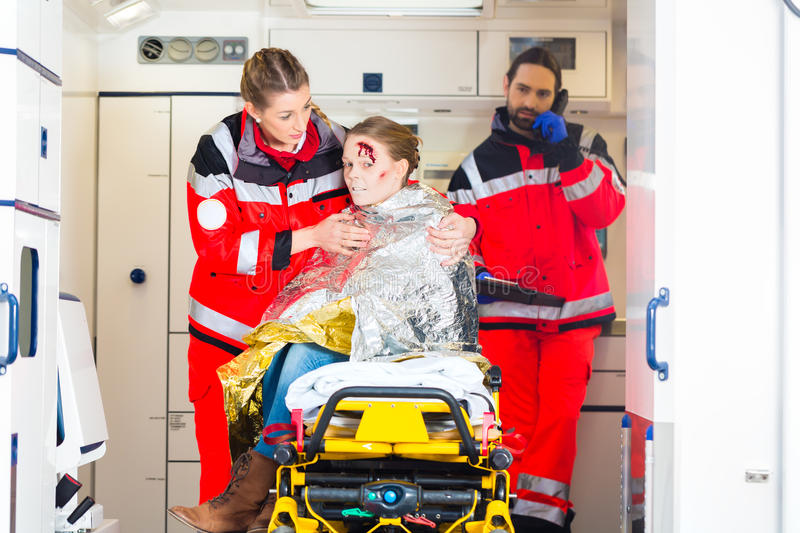 Ambulance helping injured woman. Emergency doctor and paramedic or ambulance team helping accident victim stock image