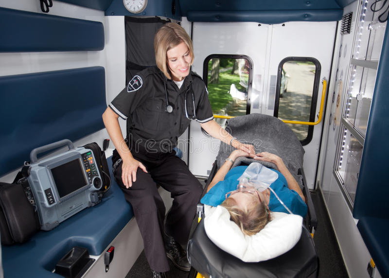 Ambulance Interior. Portrait of a paramedic in an ambulance with senior woman royalty free stock photos