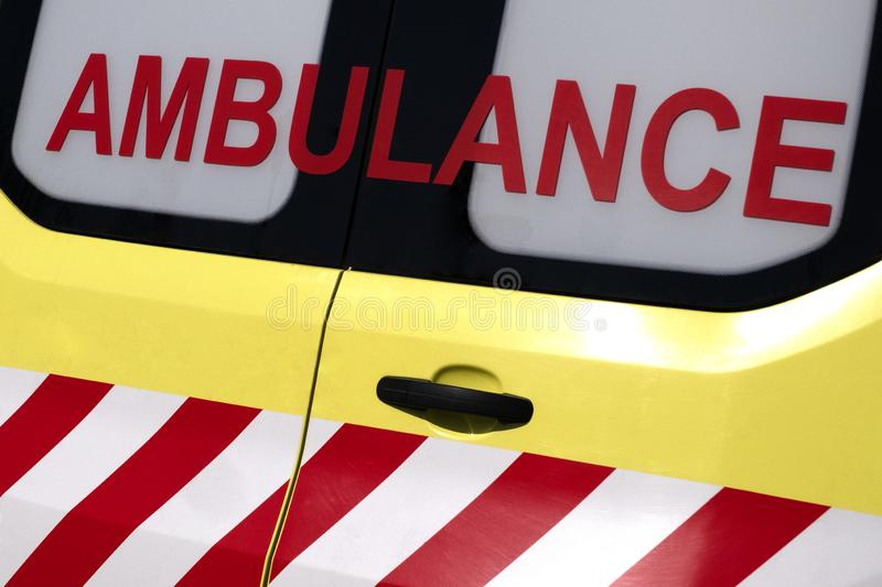 Ambulance. Red inscription on a yellow car. Emergency. Concept for design on the theme of health and helping sick people. Close-up royalty free stock photography