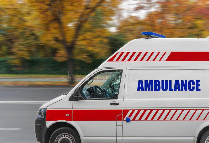 Ambulance service van driving fast on street. Close royalty free stock photography