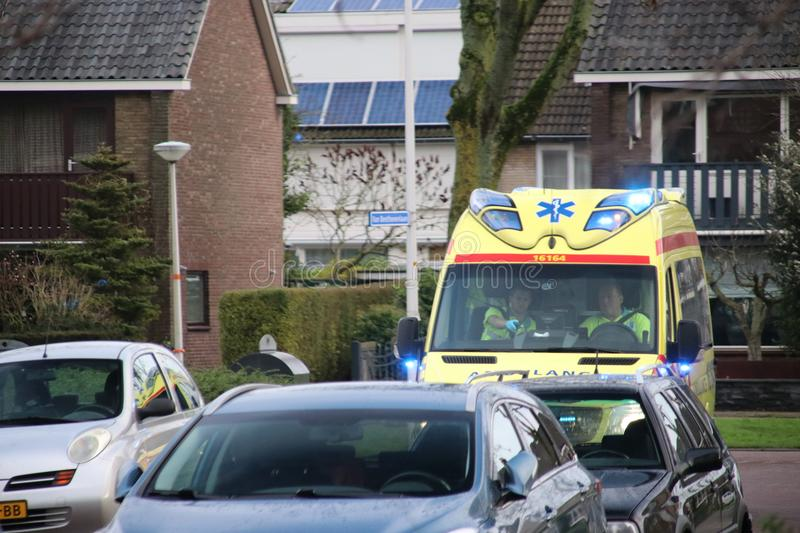 Ambulance with sirens and blue lights in a street in Nieuwerkerk aan den IJssel royalty free stock photography
