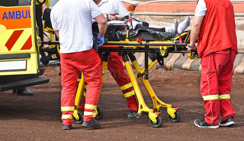Ambulance stuff with a stretcher on the sport track. In summer royalty free stock photography