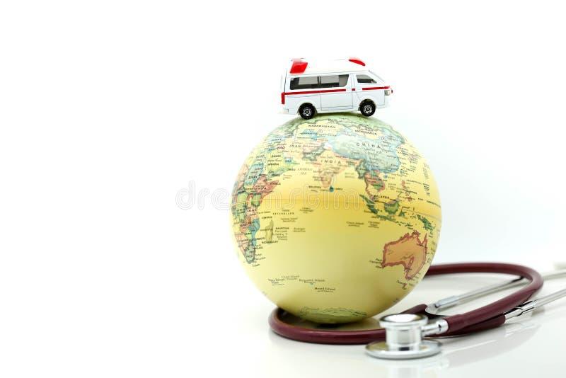Ambulancia de la medicina con el estetoscopio y el mapa del mundo, estafa de la atención sanitaria imágenes de archivo libres de regalías