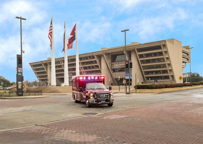 Ambulancia delante de Dallas City Hall con el americano, Tejas, y la ciudad de Dallas Flags imagen de archivo libre de regalías
