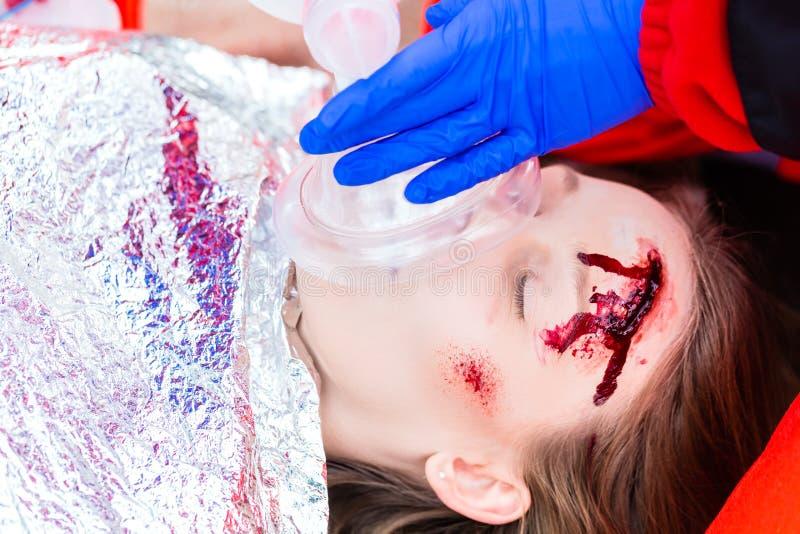 Ambulansdoktor som ger syre till det kvinnliga offret royaltyfri bild