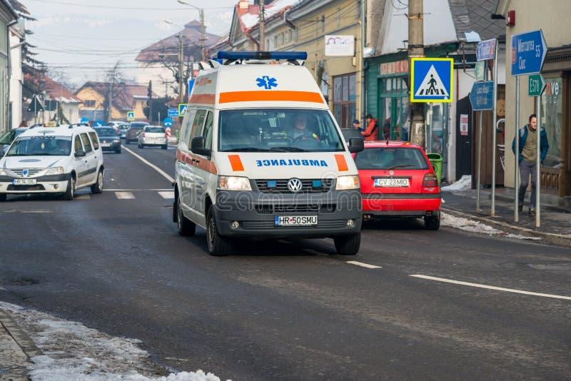Ambulansen rusar in i en liten upptagen stad royaltyfria foton
