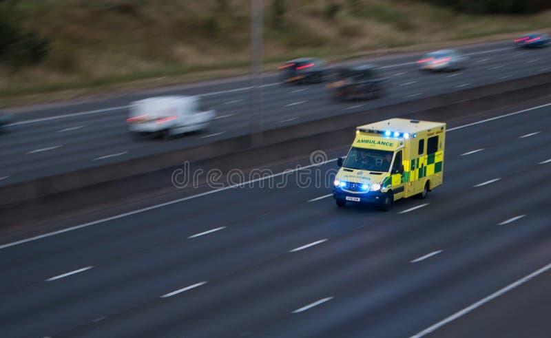 Ambulansen rusar in på motorwayen arkivfoto