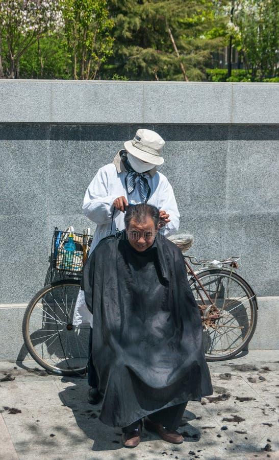 Ambulante kapper met het haar van fietsbesnoeiingen, Peking royalty-vrije stock afbeelding