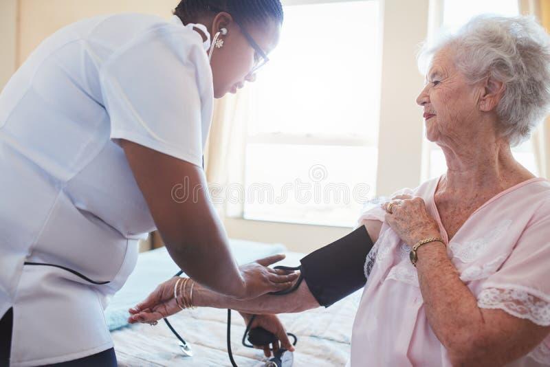 Ambulante Krankenpflegerin, die Blutdruck des Patienten nimmt lizenzfreies stockbild