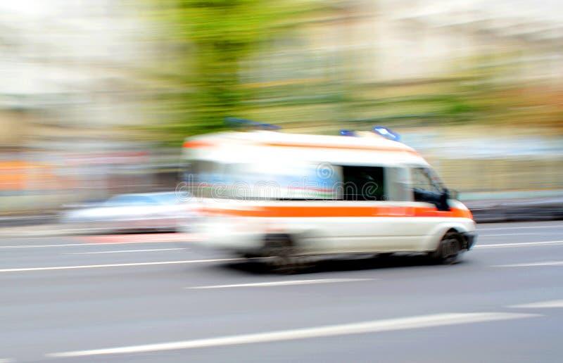 Ambulanza nel moto che guida giù la strada fotografia stock libera da diritti