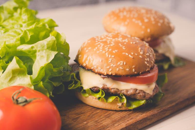 Amburger o bocadillo del  de Ð en el papel marrón Hamburguesa deliciosa del bocadillo con la carne, el queso y las verduras fres fotos de archivo libres de regalías