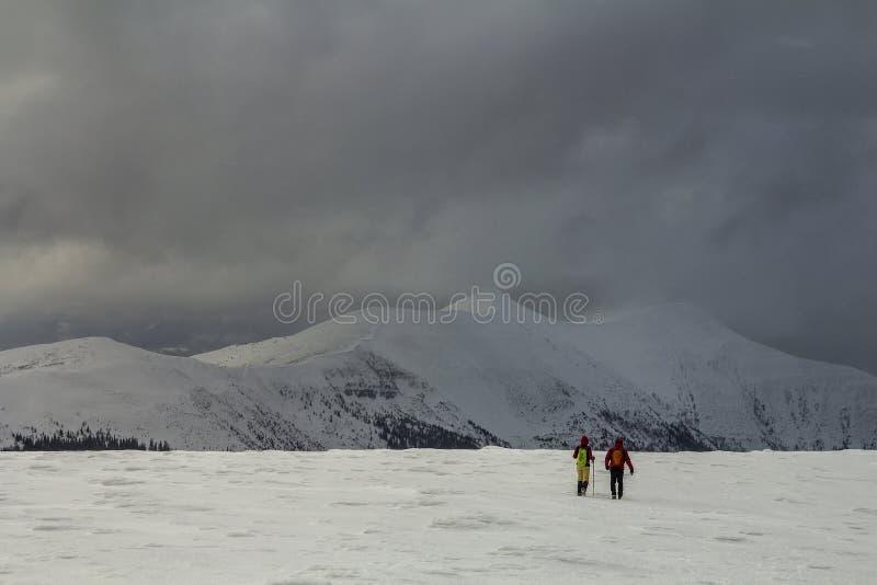amden зона около зимы Швейцарии катания на лыжах панорамы Задний взгляд 2 hikers туристов при рюкзаки идя в снежную долину к пышн стоковые изображения rf