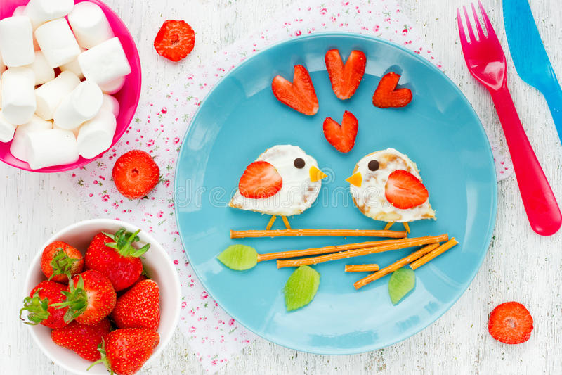 Ame el bocadillo de los pájaros de la crepe con crema y la fresa imagen de archivo libre de regalías