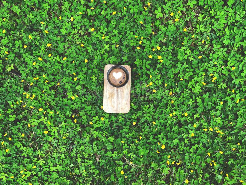 Ame el café del arte del Latte del corazón en taza negra en la bandeja de madera con las hojas verdes y poca flor amarilla imágenes de archivo libres de regalías