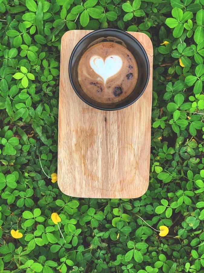 Ame el café del arte del Latte del corazón en taza negra en la bandeja de madera con las hojas verdes y poca flor amarilla fotos de archivo