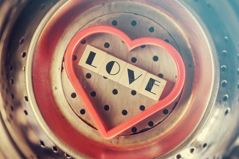 Ame el mensaje escrito con los bloques de madera dentro de un corazón rojo fotos de archivo