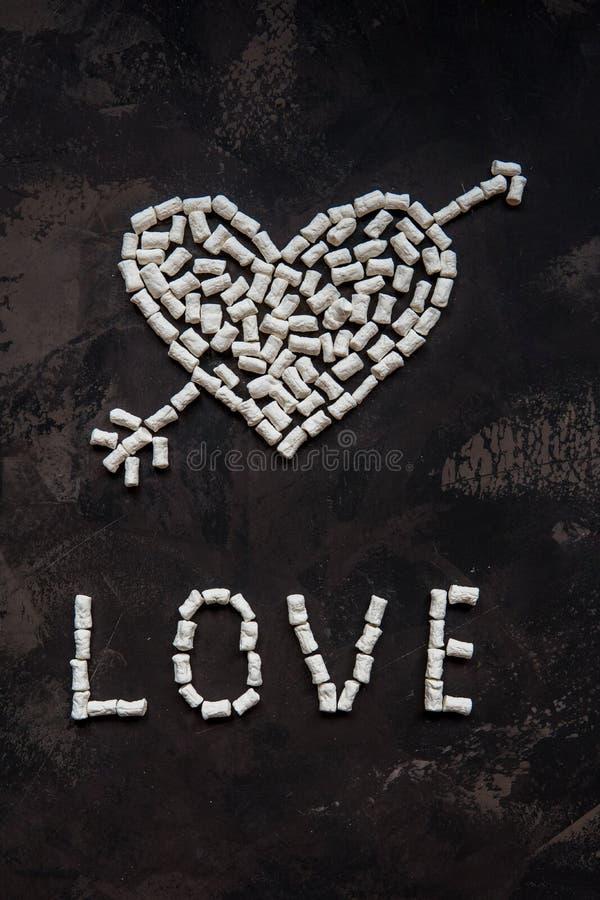 Ame el texto hecho de la melcocha blanca del corazón, decoración para el amor foto de archivo