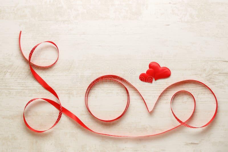Ame escrito com a fita vermelha no fundo de madeira fotos de stock royalty free