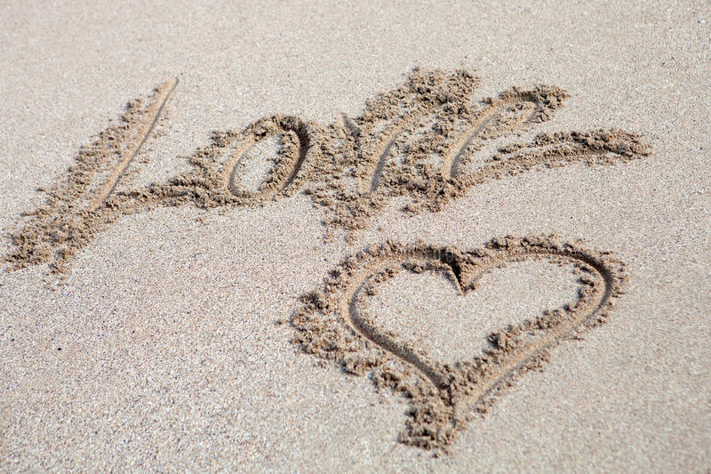 Ame escrito na areia com um desenho da lareira foto de stock royalty free