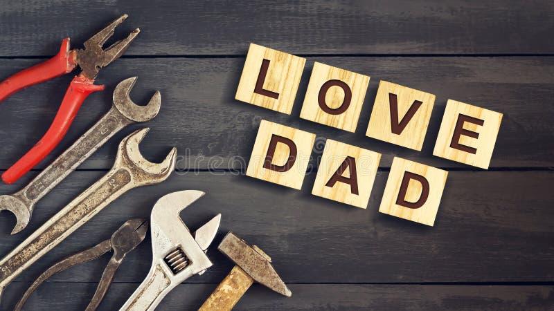 Ame a inscrição do paizinho em cubos de madeira com ferramentas de funcionamento em um fundo de madeira Dia de pai feliz Cumprime fotografia de stock