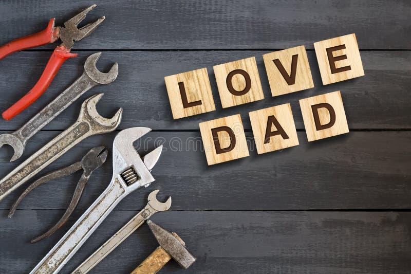 Ame a inscrição do paizinho em cubos de madeira com ferramentas de funcionamento em um fundo de madeira Dia de pai feliz Cumprime foto de stock royalty free