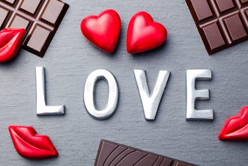 Ame la palabra, el coraz?n y los caramelos de chocolate formados los labios con las barras de chocolate en fondo de la pizarra fotos de archivo