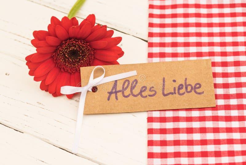 Ame la tarjeta de felicitación, con el texto Alles Liebe del geman, y la flor roja romántica fotos de archivo