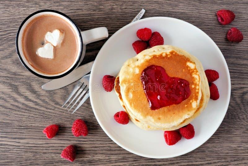 Ame las crepes del desayuno del concepto, el chocolate caliente y las frambuesas sobre la madera imagen de archivo