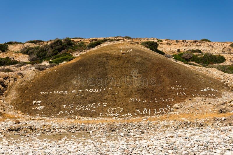 Ame las escrituras inscritas por los guijarros dejados por los turistas en la playa de Aphrodite Rock, Chipre imágenes de archivo libres de regalías