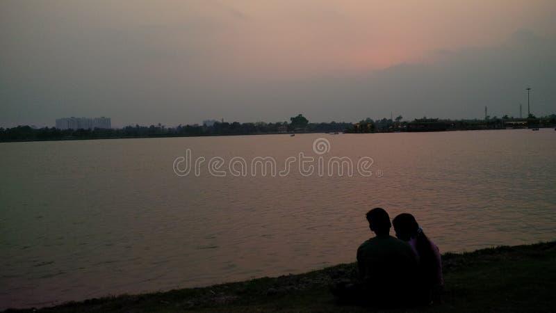 Ame las metas de los pares al lado del río en la puesta del sol fotografía de archivo libre de regalías