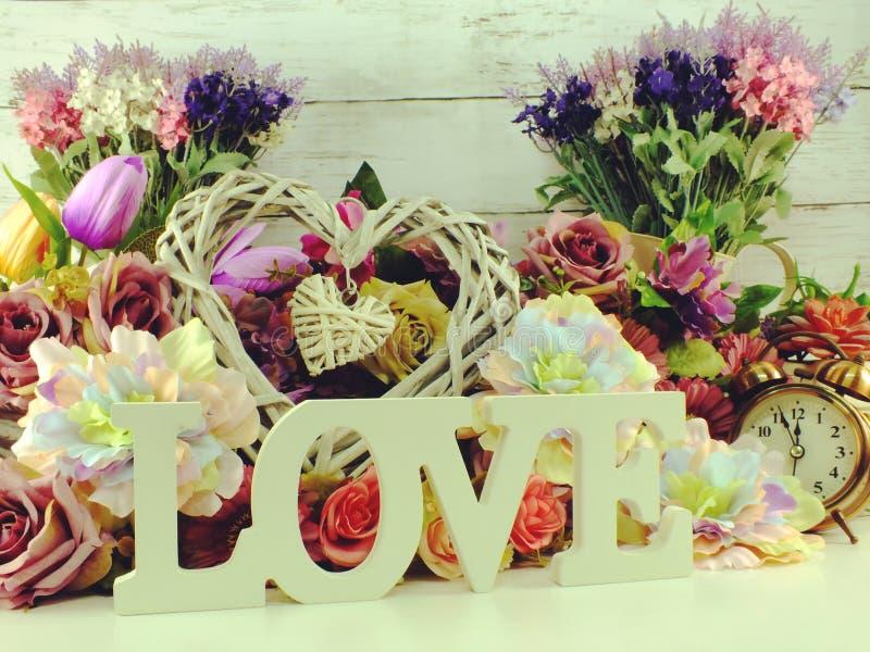 Ame a letra de madeira da palavra com a decoração das flores artificiais imagem de stock royalty free