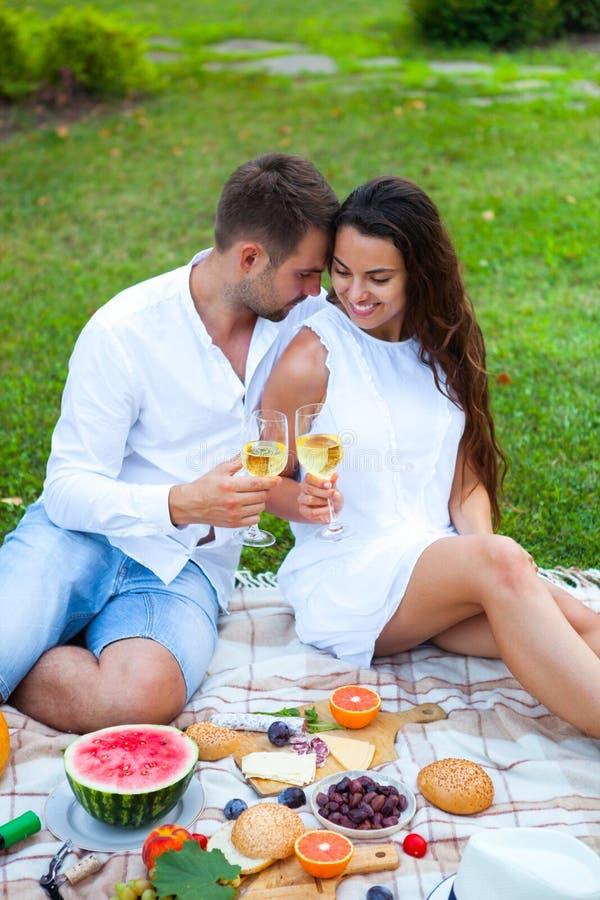 Ame los pares en cesta de la comida campestre del verano en la hierba verde Comida y fotos de archivo