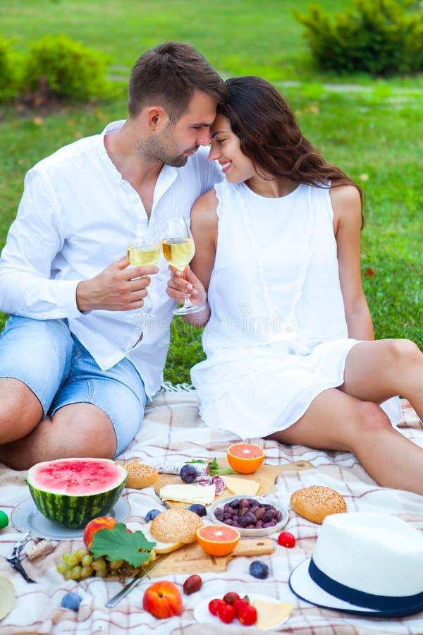 Ame los pares en cesta de la comida campestre del verano en la hierba verde Comida y fotos de archivo libres de regalías