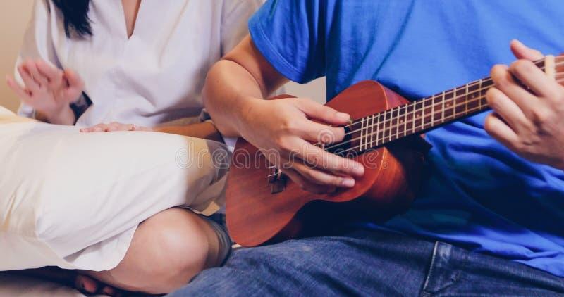 Ame los pares que tocan el ukelele y la guitarra en cama fotografía de archivo