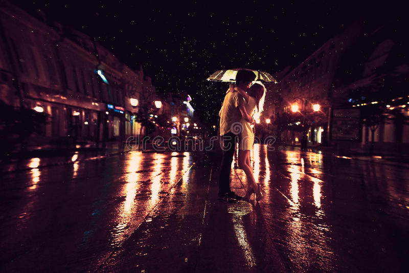 Ame na chuva/silhueta de pares de beijo sob o guarda-chuva imagens de stock royalty free