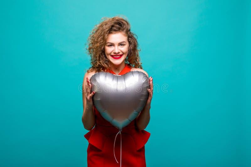 Ame o balão dado forma de sorriso da terra arrendada da mulher coração vermelho Jovem mulher bonita bonito no amor Modelo fêmea c fotos de stock