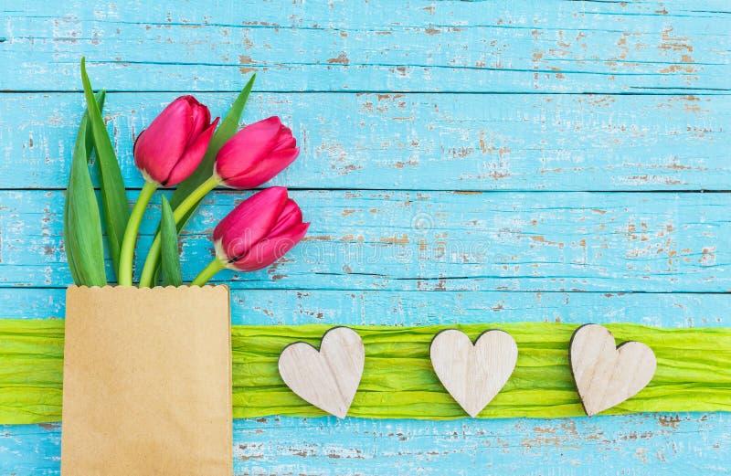 Ame o fundo com corações de madeira rústicos e as flores vermelhas das tulipas na luz - madeira azul foto de stock