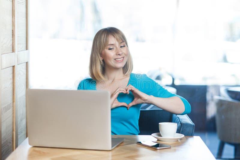 Ame-o! O retrato da moça feliz romântica com cabelo louro na blusa azul está sentando-se no café e está olhando-se a exposição co fotos de stock