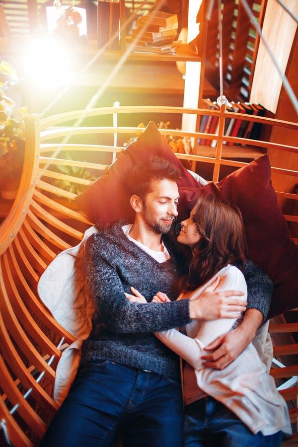 Ame o retrato de um par novo afetuoso que encontra-se em uma rede que olha afastado de sorriso Jardim romântico do homem e da mul fotografia de stock