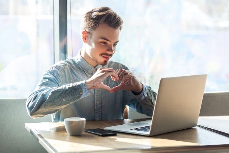 Ame-o! O retrato do noivo novo feliz romântico na camisa azul está sentando-se no café e está mostrando-se a sua amiga uma forma  imagens de stock