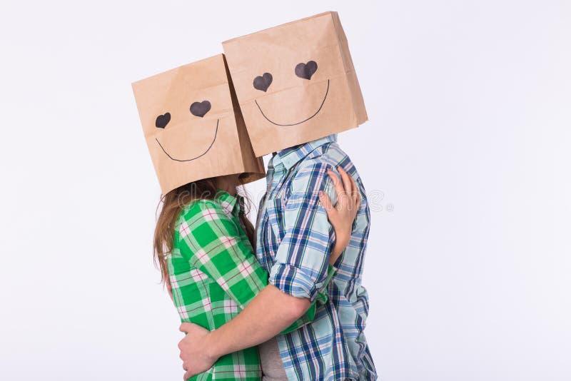 Ame os pares que cobrem suas caras com o saco de papel sobre o fundo branco imagem de stock royalty free