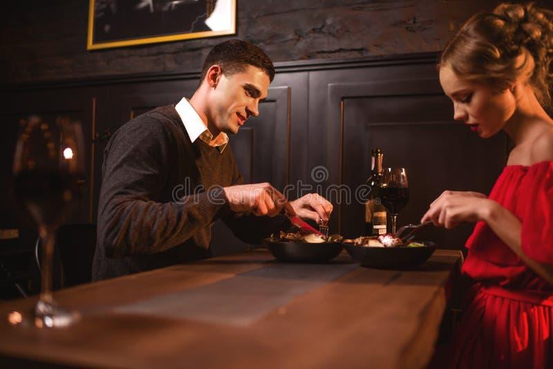 Ame os pares que comem no restaurante, data romântica imagem de stock royalty free